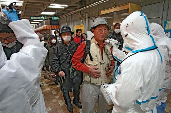 يُفحص رجل بحثًا عن تعرضه للإشعاع بعد إجلائه من منطقة الحجر الصحي حول محطة للطاقة النووية في محافظة فوكوشيما باليابان، والتي تضررت في 11 مارس 2011 جراء الزلزال والتسونامي.