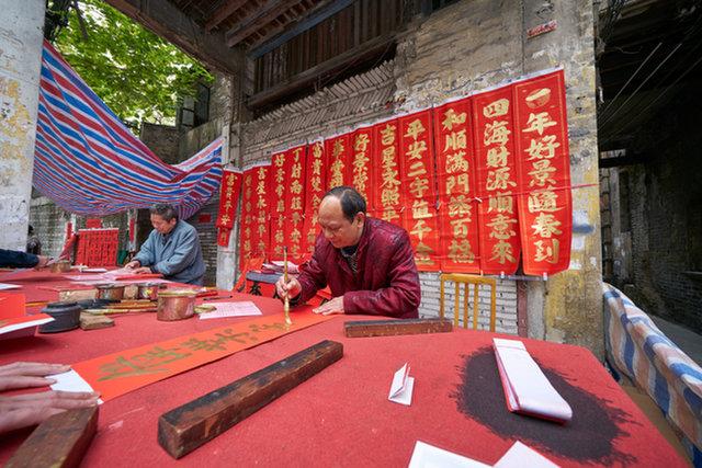 خطاط في فوشان، الصين يصنع ثنائيةً - لافتات يتمنى الناس فيها الحظ السعيد والعمر الطويل - لمهرجان الربيع.