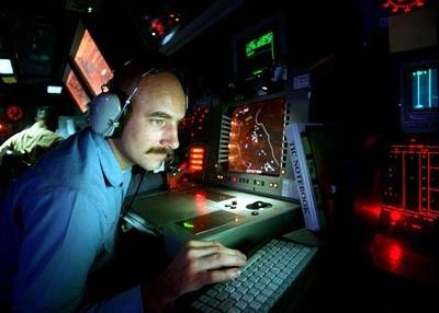 مختص التشغيل Gilbert Lundgren يشغل تجهيزات الرادار في مركز معلومات المدمرة الأمريكية Carney